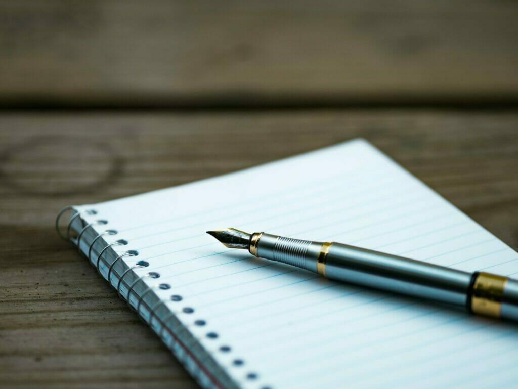 Cuaderno en blanco sobre el que yace un bolígrafo - Este artículo habla sobre el plan dignidad y la reforma migratoria integral de biden